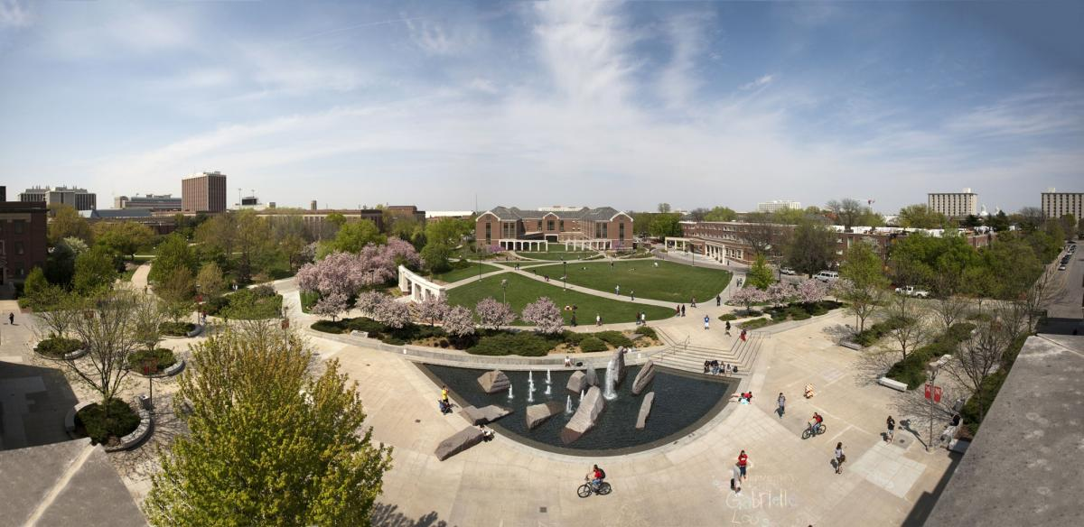 panorama of campus from the Nebraska Union showcasing students, the fountain, green space, and campus buildings